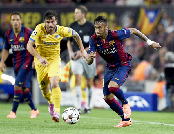 Barcelona's Brazilian forward Neymar da Silva Santos Junior (R) vies with Apoel's Portuguese midfielder Tiago Gomes (L) during the UEFA Champions League football match FC Barcelona vs APOEL FC at the Camp Nou stadium in Barcelona on September 17, 2014.  AFP PHOTO / LLUIS GENE