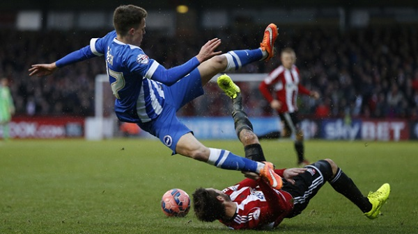 BRENTFORD, ENGLAND - JANUARY 03: Solly March of Brighton & Hove Albion is tackled by Tommy Smith of Brentford during the FA Cup Third Round match between Brentford v Brighton & Hove Albion at Griffin Park on January 3, 2015 in Brentford, England.  (Photo by Steve Bardens/Getty Images)